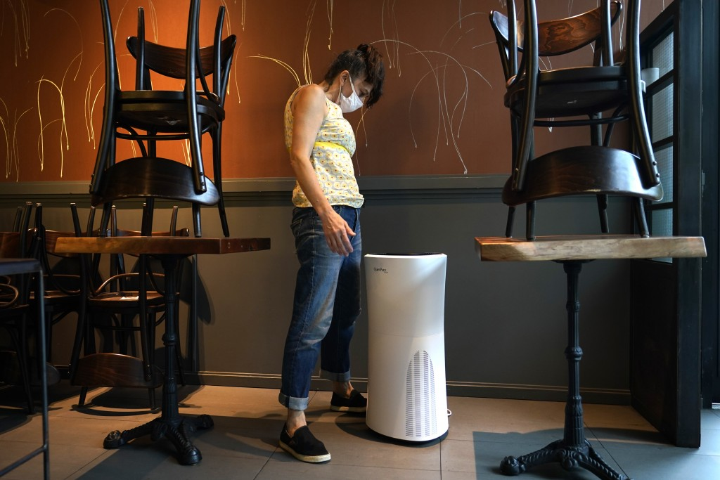 Mama Fox owner Samantha DiStefano looks at an air purifier she'll need when she opens the indoor portion of her restaurant and bar to patrons, Tuesday...
