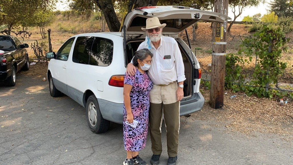 Wildfire evacuees Mike Christianson and his wife Mluz Torres stand in front their minivan outside a church shelter in Napa, Calif. on Tuesday, Sept. 2...