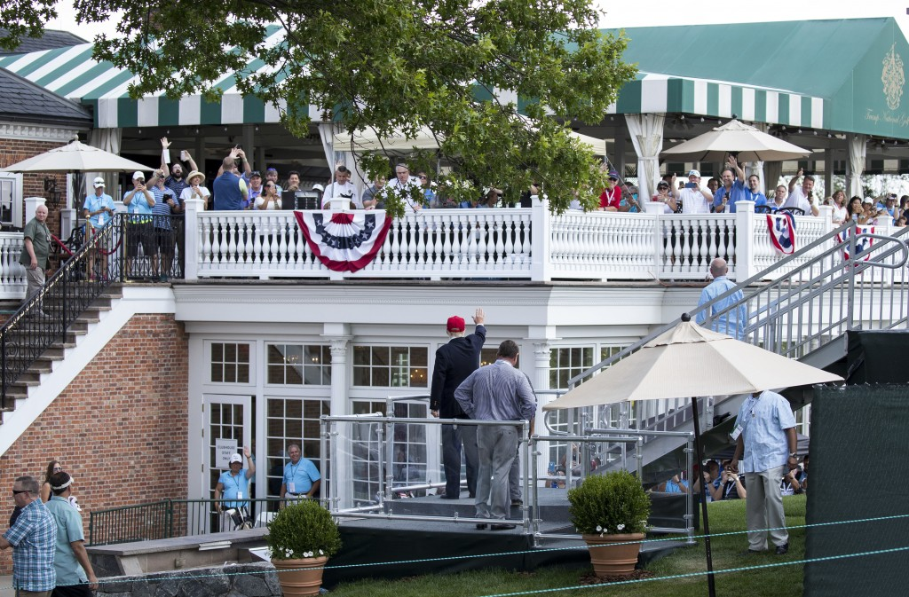 FILE - In this July 15, 2017 file photo, President Donald Trump turns to wave to people gathered at the clubhouse as his walks to his presidential vie...