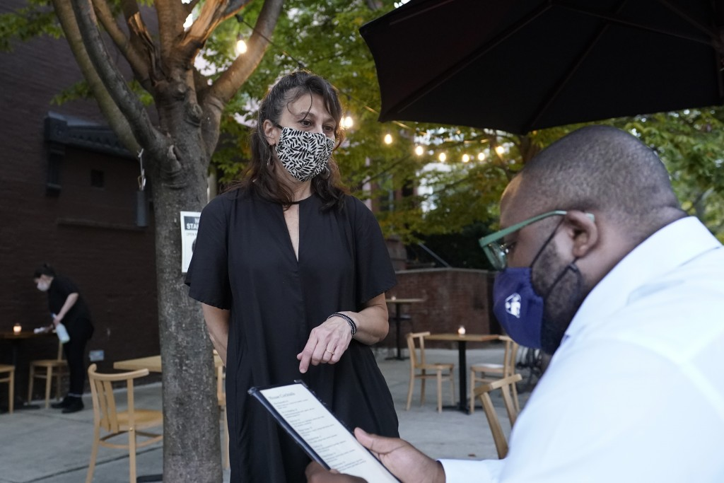 Mama Fox bar and restaurant owner Samantha DiStefano, left, shows a menu to customer Rashad Moore, Tuesday, Sept. 29, 2020, in New York, as Moore prep...