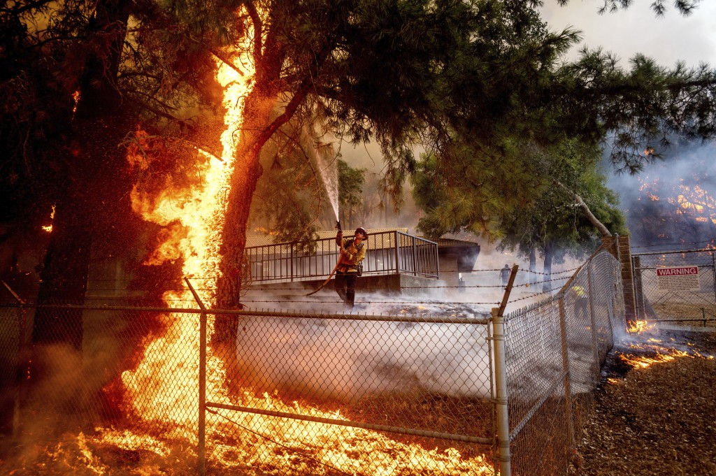Cal Fire Capt. Jesse Campbell works to save the Louis Stralla Water Treatment Plant as the Glass Fire burns in St. Helena, Calif., on Sunday, Sept. 27...