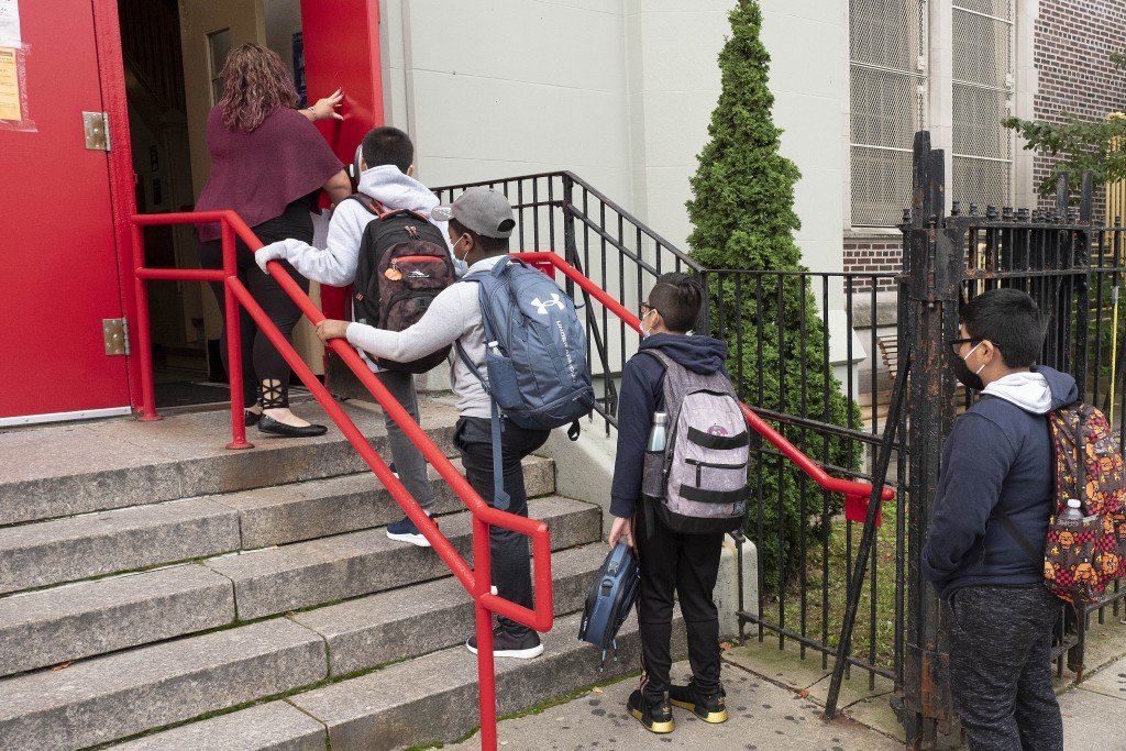 A teacher leads her students into an elementary school in the Brooklyn borough of New York on Tuesday, Sept. 29, 2020, as hundreds of thousands of ele...