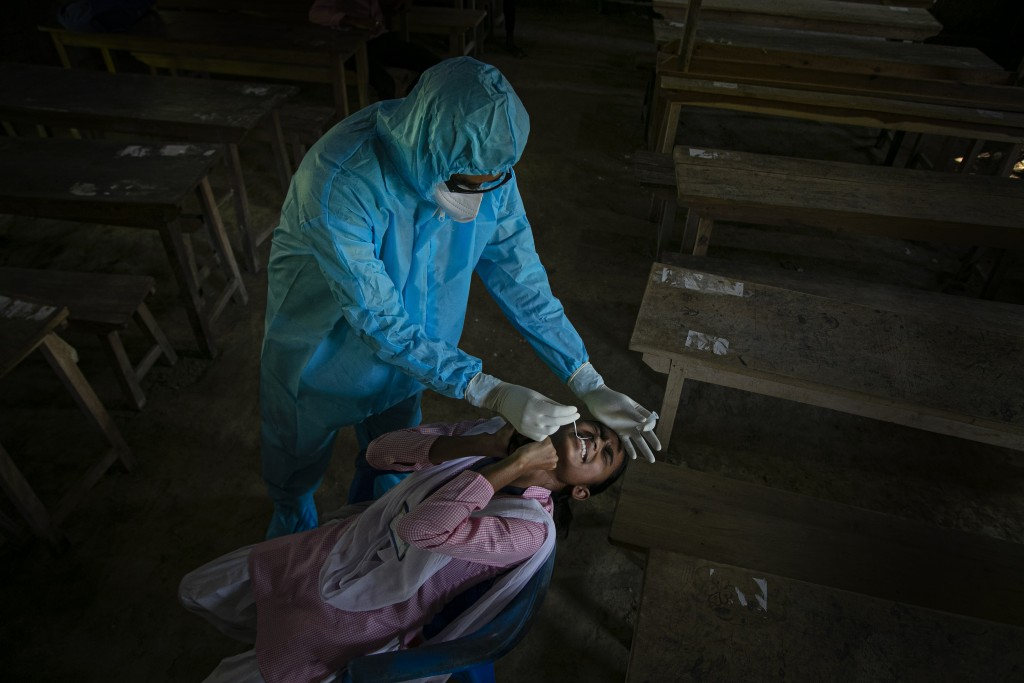An Indian health worker takes a nasal swab sample of a student to test for coronavirus after classes started at a college in Jhargaon village, outskir...