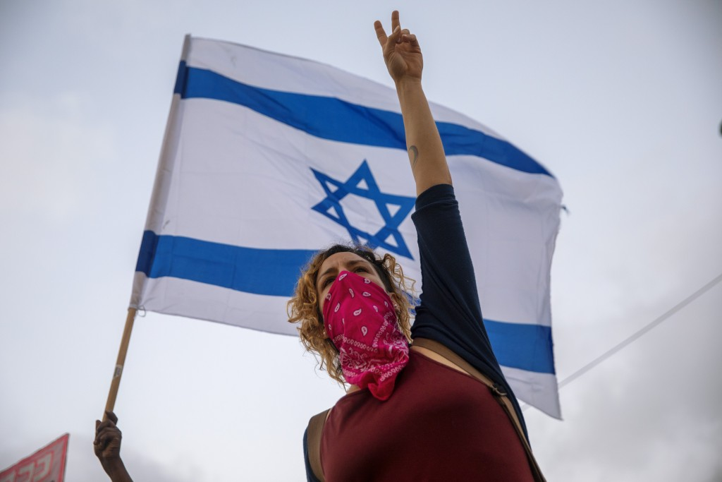 Israeli protesters wave flags and chant slogans during a demonstration against parliament's plans to ban them from protesting during the current natio...