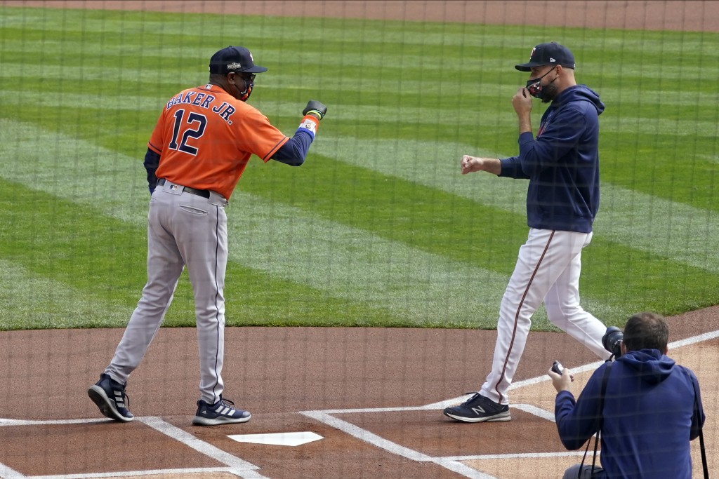 Minnesota Twins manager Rocco Baldelli, right, and Houston Astros manager Dusty Baker, Jr. greet each other before the first inning of an American Lea...