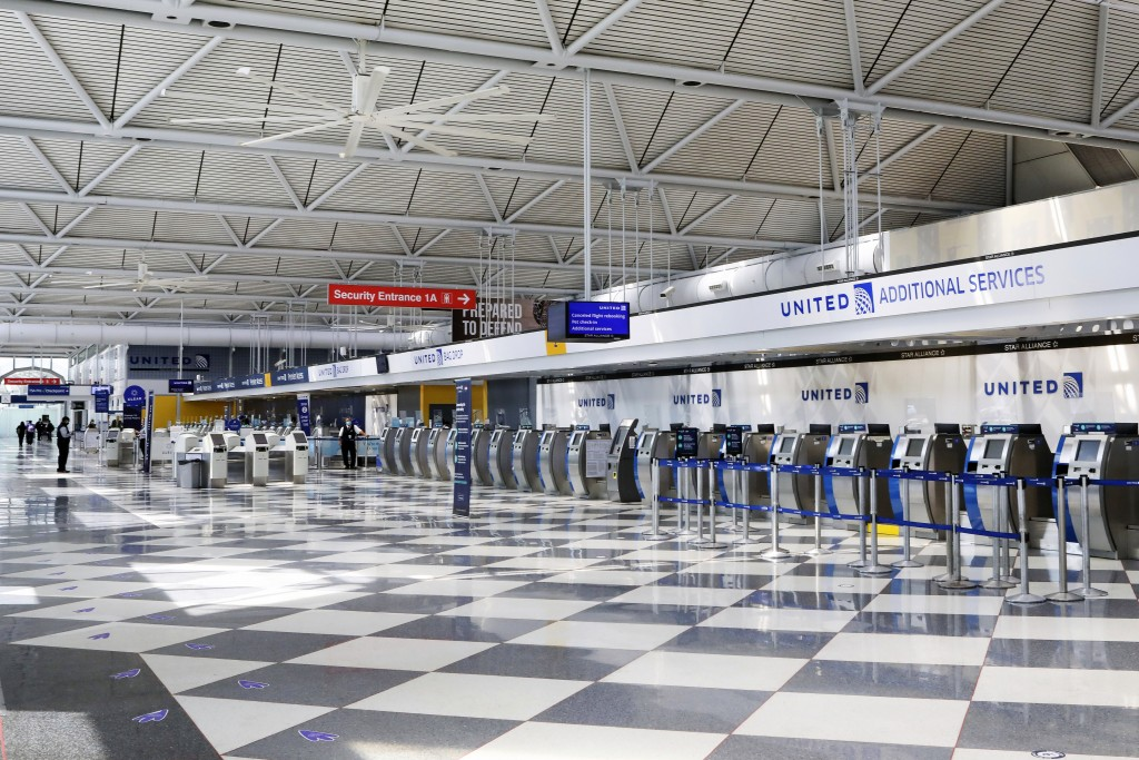 FILE - In this June 25, 2020, file photo, rows of United Airlines check-in counters at O'Hare International Airport in Chicago are unoccupied amid the...