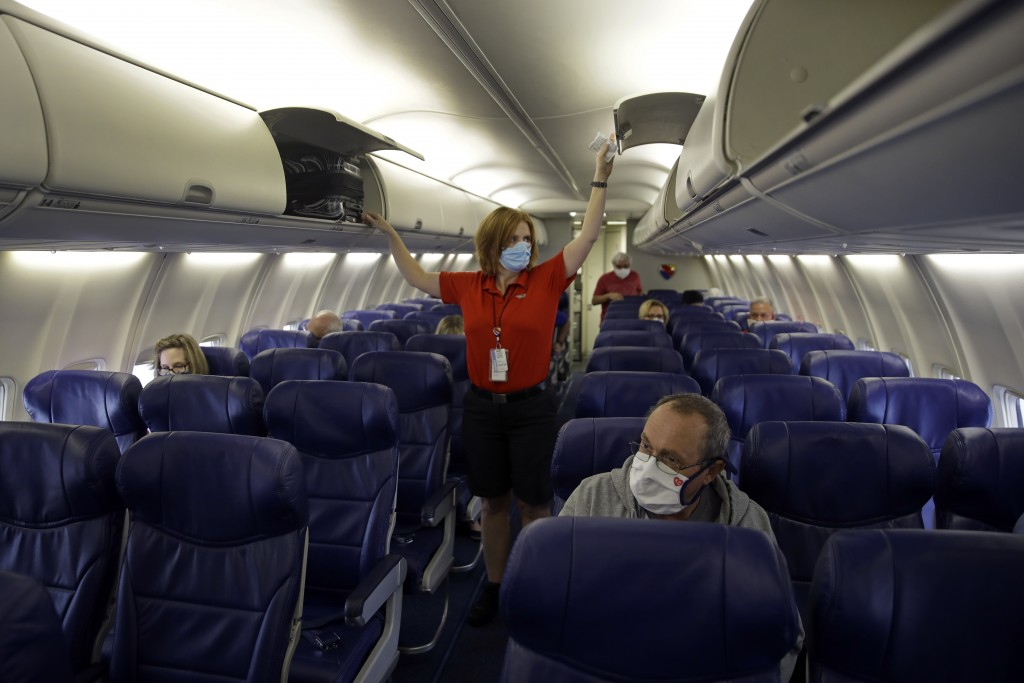 FILE - In this May 24, 2020, file photo, a Southwest Airlines flight attendant prepares a plane bound for Orlando, Fla. for takeoff at Kansas City Int...