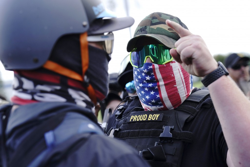 FILE - In this Sept. 26, 2020 file photo, a right-wing demonstrator gestures toward a counter protester as members of the Proud Boys and other right-w...