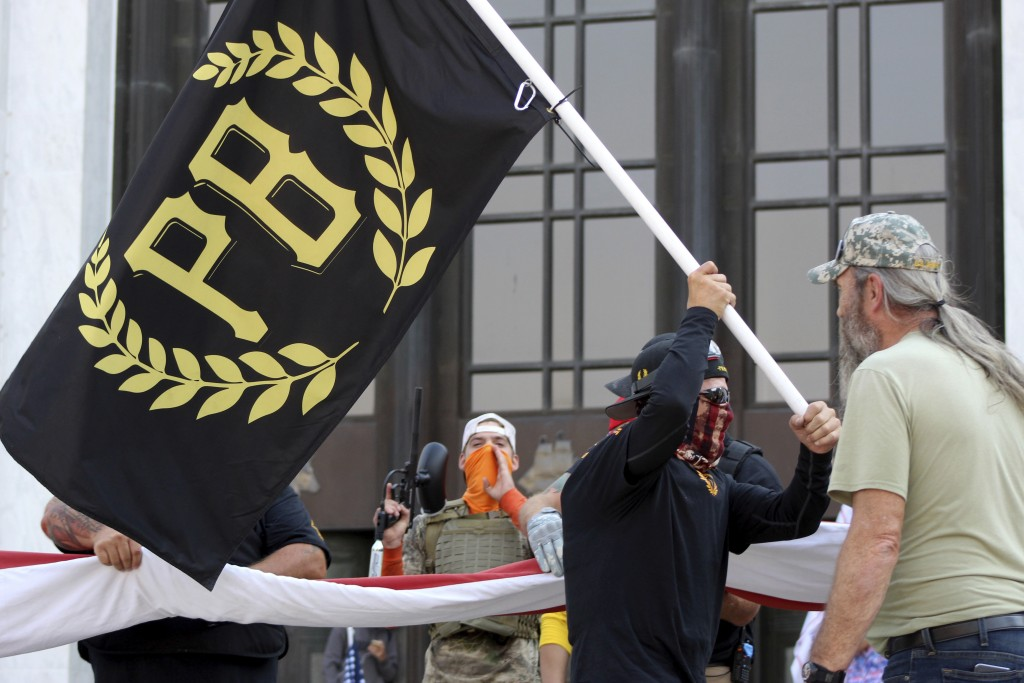 FILE - In this Sept. 7, 2020 photo, a protester carries a Proud Boys banner, symbol of a right-wing group, while other members start to unfurl a large...