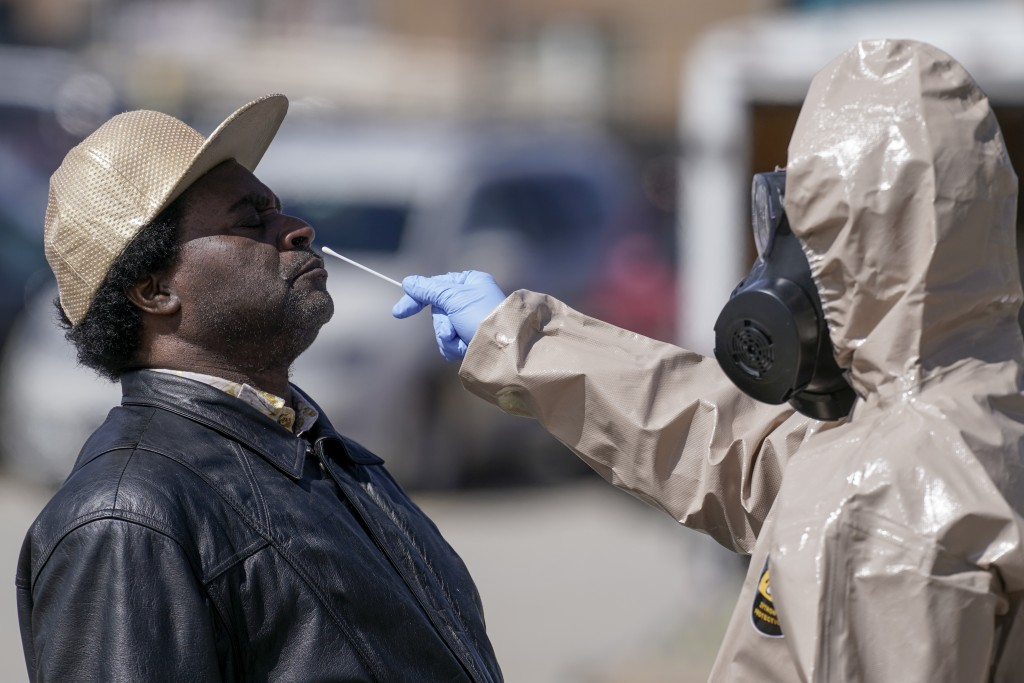 FILE - In this May 11, 2020, file photo, Wisconsin National Guard members administer COVID-19 tests in a parking lot  in Milwaukee. The coronavirus ti...