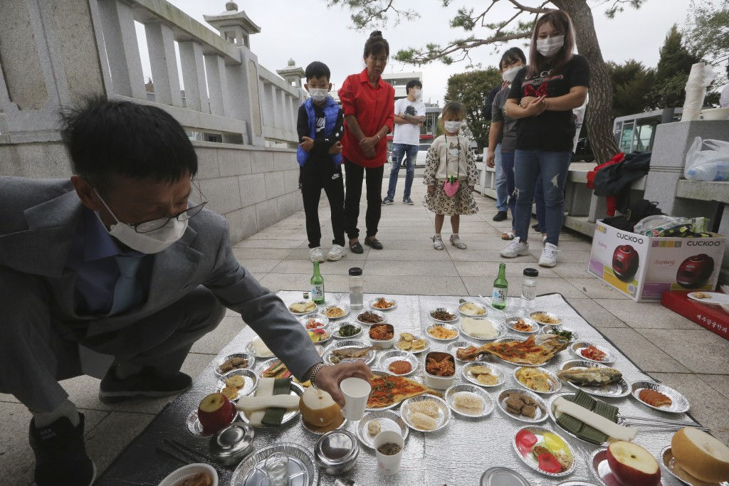 North Korean defector Han Hong-geun, left, and his family members pay respect to their ancestors in North Korea to celebrate the Chuseok, the Korean v...