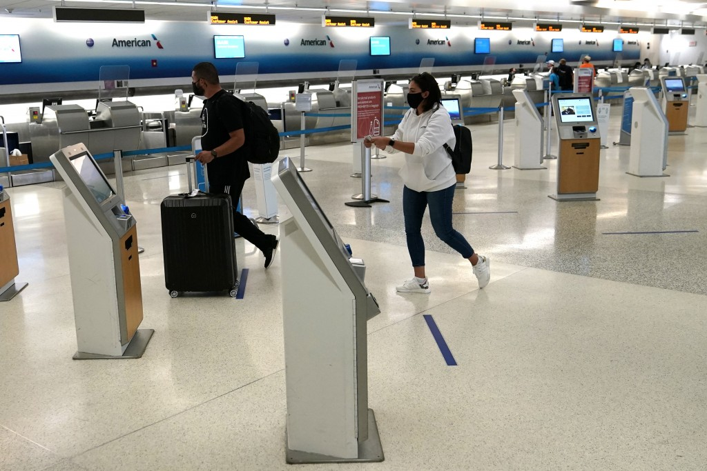 Passengers walk through a largely empty check-in area for American Airlines at Miami International Airport during the coronavirus pandemic, Wednesday,...