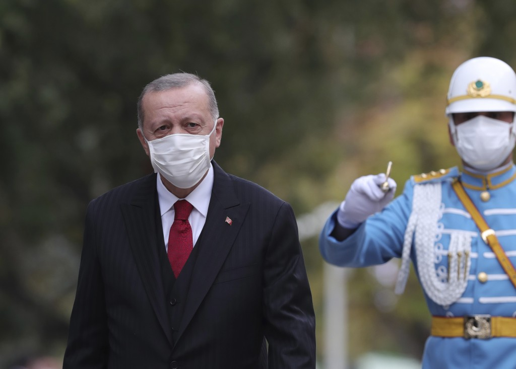 Turkey's President Recep Tayyip Erdogan, wearing a face mask to help prevent the spread of the coronavirus, inspects a military honour guard at the pa...