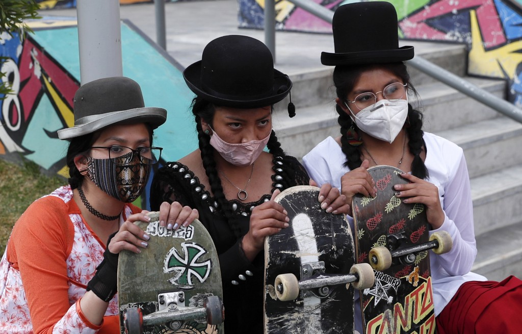 """Yanira Villarreal, left, Ayde Choque, center, and Milenda Limachi, wearings masks amid the COVID-19 pandemic and dressed as a """"Cholita"""" pose for a pho..."""