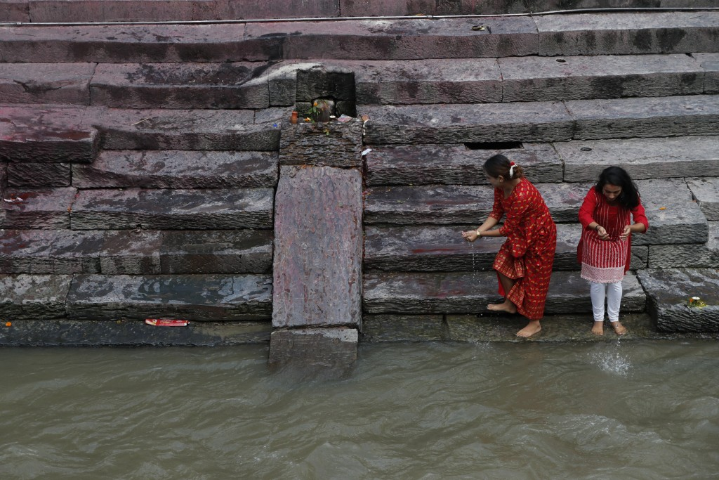 Nepalese devotees collect water from the Bagmati river to perform rituals as the Pashupati temple was closed as a precautionary measure against the sp...