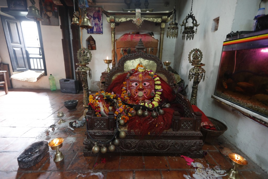 The mask of Lakhe, a traditional mask dancer worshipped as a god, is covered with floral garlands after rituals were performed during Indrajatra festi...