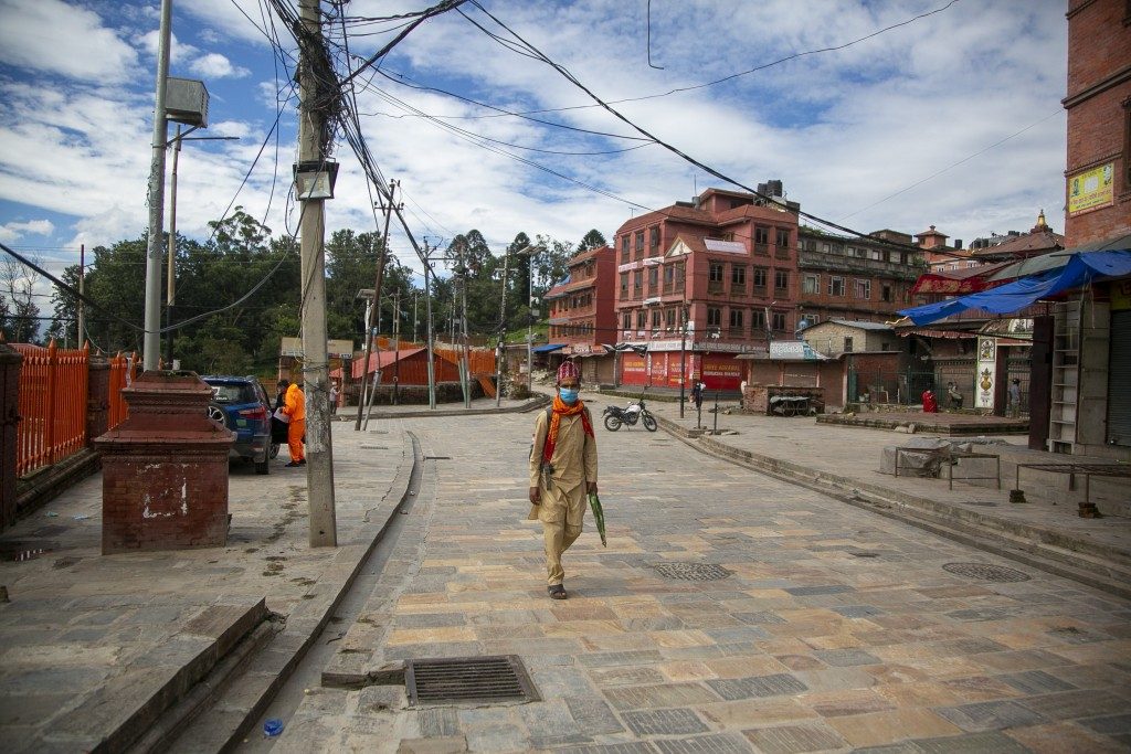 A Nepalese Hindu Priest walks at the deserted Pashupatinath temple premises during Teej festival in Kathmandu, Nepal, Friday, Aug. 21, 2020. Autumn is...