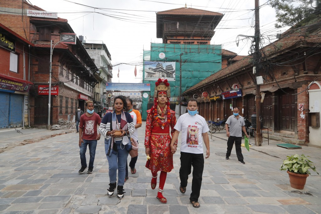 Living God Ganesh, center, walks back home after a ritual was performed during Indrajatra festival as the festival was canceled to control the spread ...