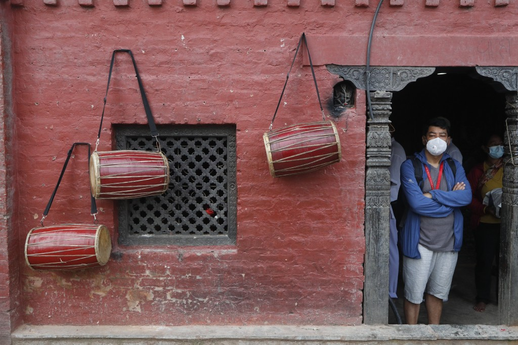 A Nepalese man waits for his turn to perform rituals as traditional drums are seen hanging on the wall during Gunla festival at Swayembhunath Stupa in...