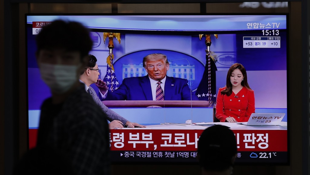 A man wearing a face mask walks near a TV screen reporting about U.S. President Donald Trump and first lady Melania Trump during a news program with a...