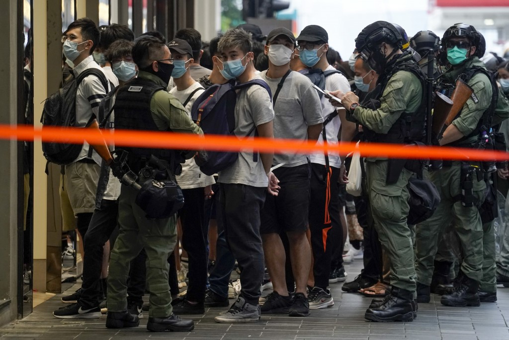 Police detain people inside a cordoned area during China's National Day in Causeway Bay, Hong Kong,