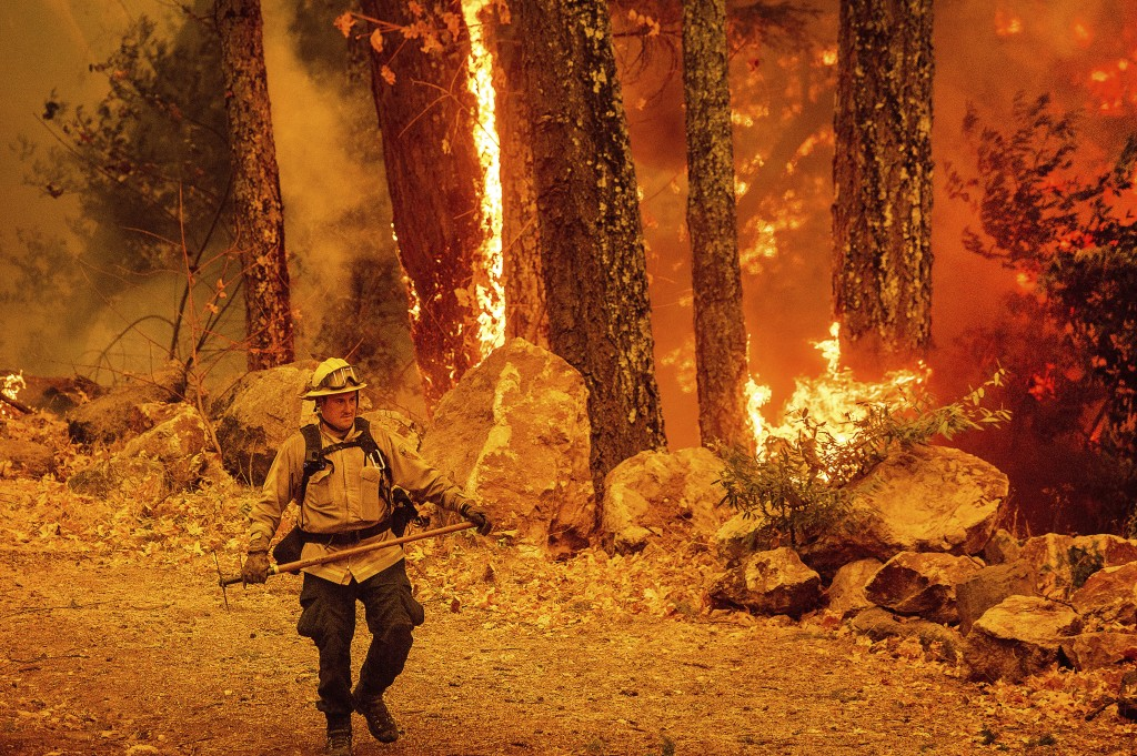 A firefighter walks a path as the Glass Fire burns along Highway 29 in Calistoga, Calif., on Thursday, Oct. 1, 2020. (AP Photo/Noah Berger)
