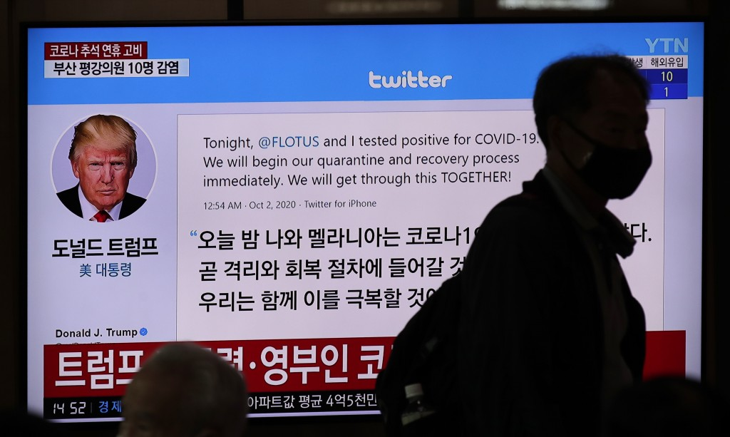 A man wearing a face mask walks near a TV screen showing an image of U.S. President Donald Trump's twitter during a news program at the Seoul Railway ...