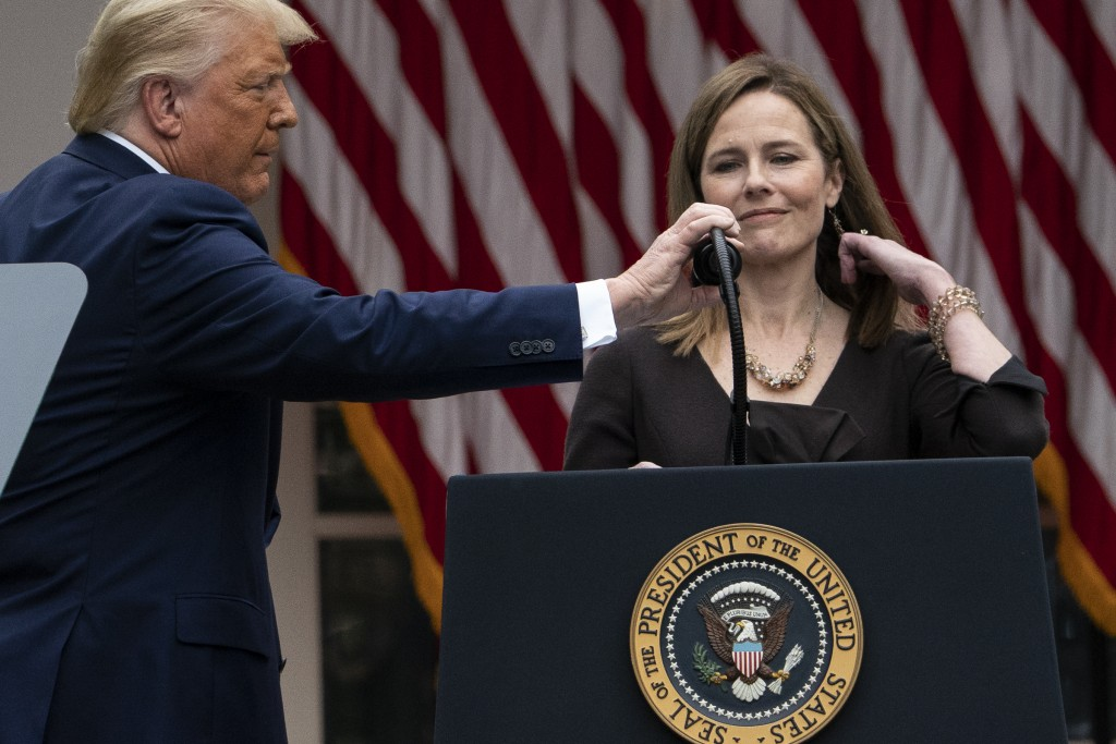 President Donald Trump adjusts the microphone after he announced Judge Amy Coney Barrett as his nominee to the Supreme Court, in the Rose Garden at th...