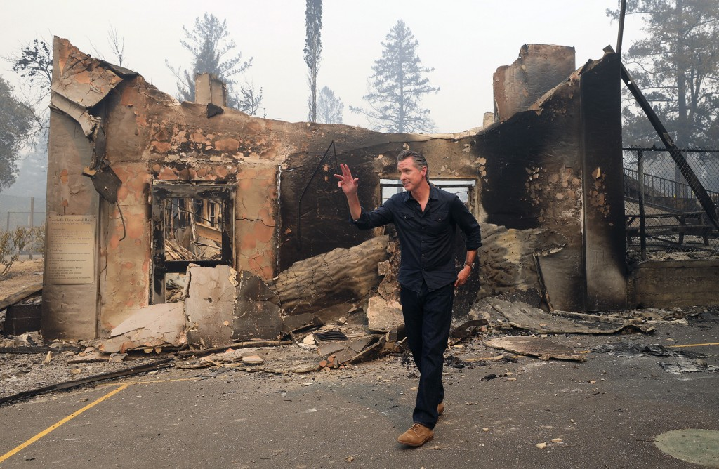 California Governor Gavin Newsom waves as he leaves the burned portion of Foothills Elementary School following a press conference near St. Helena, Ca...