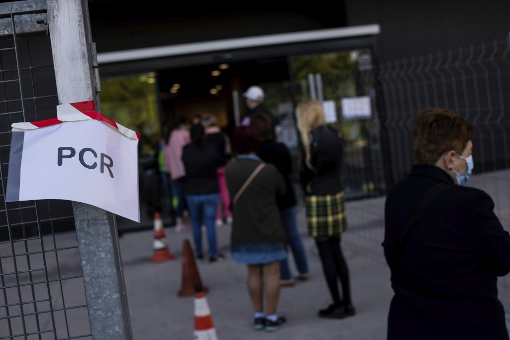 People queue for a rapid antigen test for COVID-19 in the southern neighbourhood of Vallecas in Madrid, Spain, Thursday, Oct. 1, 2020. Madrid and its ...