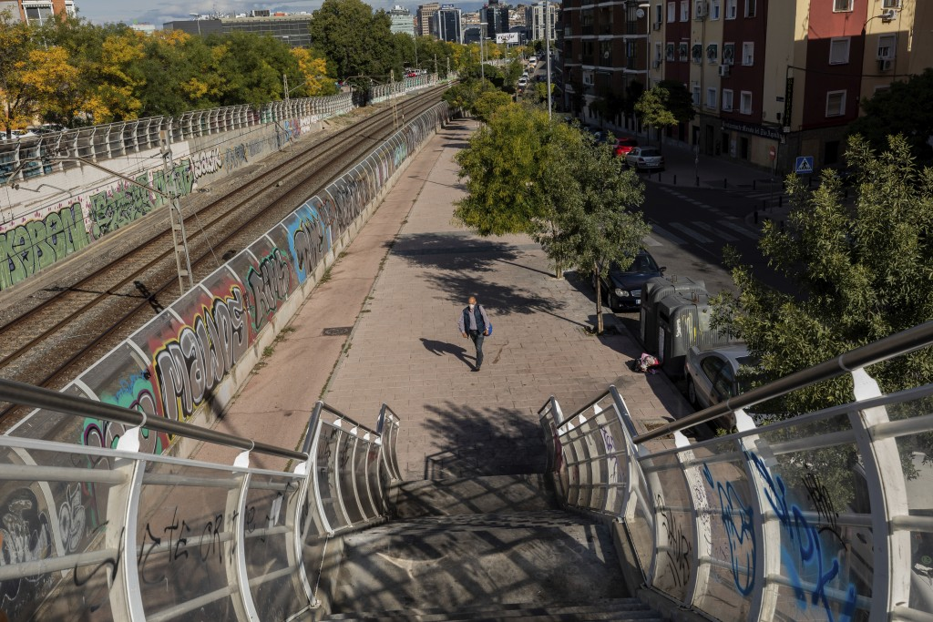 A man wearing a face mask to prevent the spread of the coronavirus walks in the southern neighbourhood of Vallecas in Madrid, Spain, Thursday, Oct. 1,...