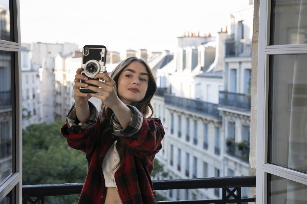 """This image released by Netflix shows Lily Collins in a scene from the series """"Emily in Paris,"""" premiering on Friday. (Stephanie Branchu/Netflix via AP..."""