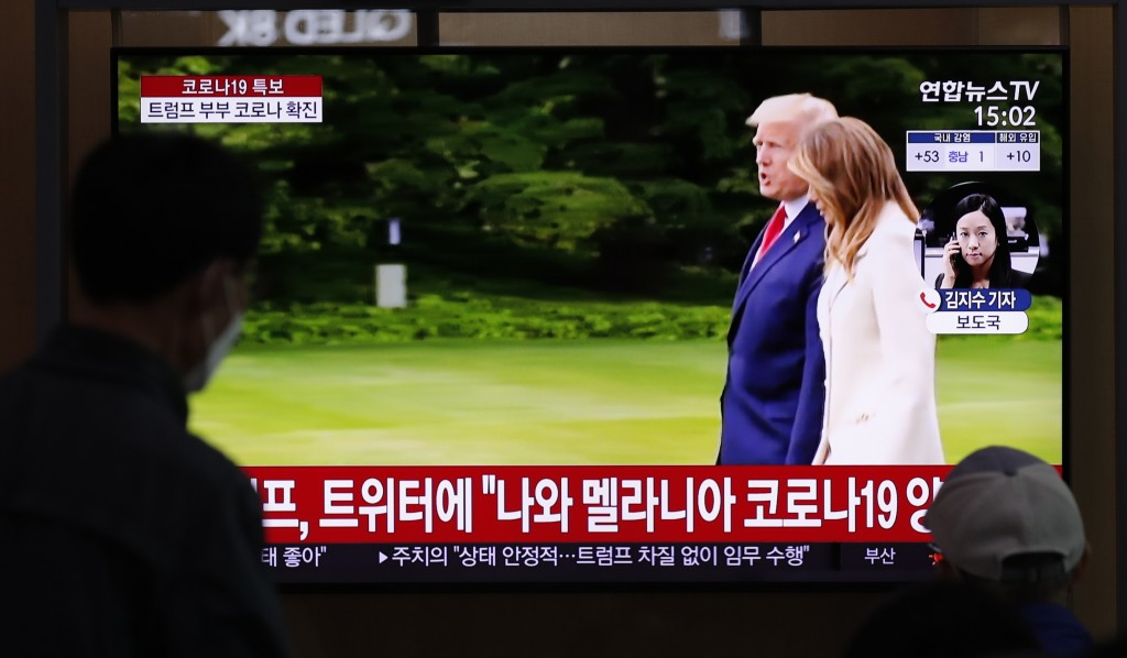 People wearing face masks watch a TV screen reporting about U.S. President Donald Trump and first lady Melania Trump during a news program with a file...