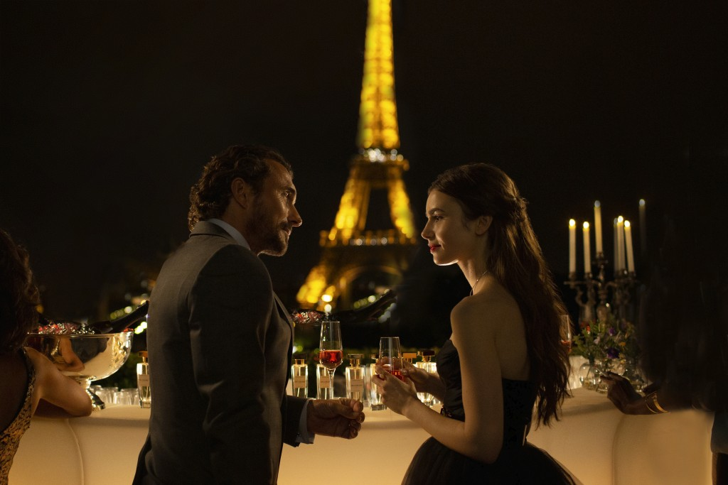 """This image released by Netflix shows William Abadie, left, and Lily Collins in a scene from the series """"Emily in Paris,"""" premiering on Friday. (Carole..."""