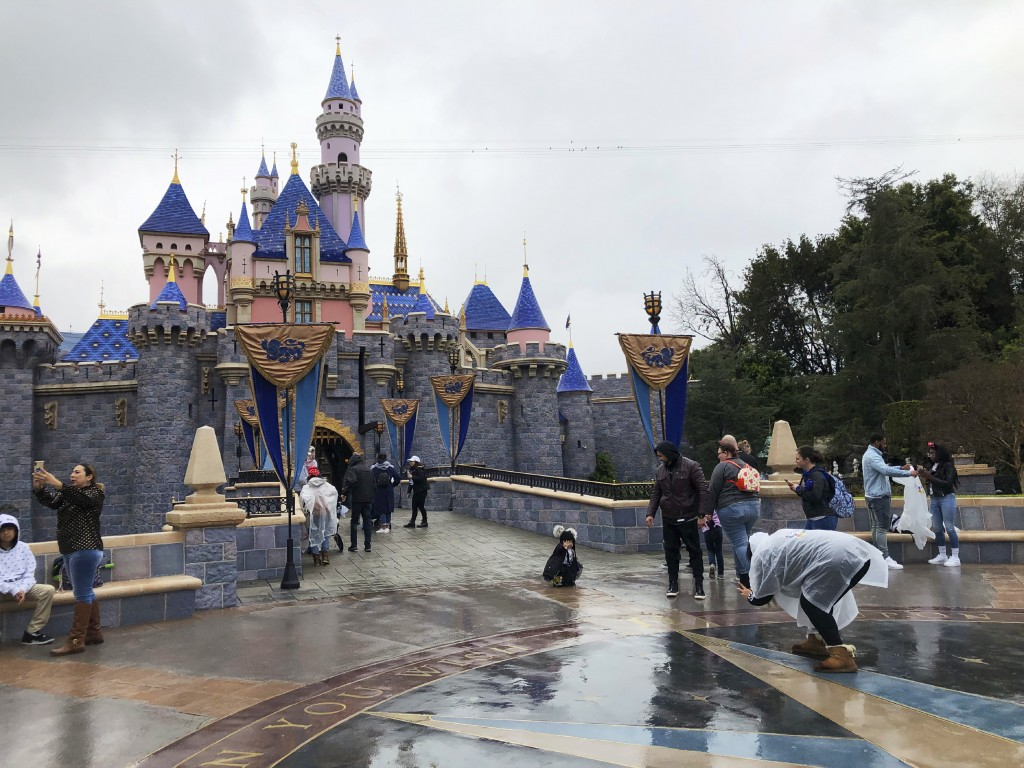 FILE - In this March 13, 2020 file photo, visitors take photos at Disneyland in Anaheim, Calif., the last day the park was open due to the COVID-19 pa...