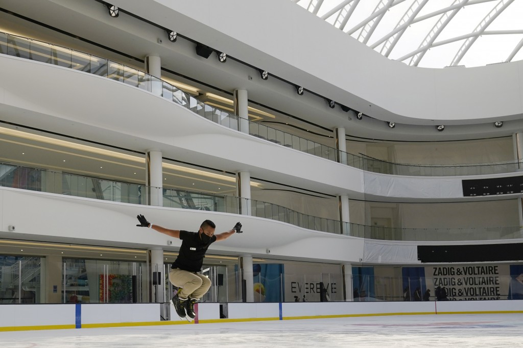 Employee Alex Tropel leaps while practicing his skating moves at a nearly empty ice rink inside the American Dream Mall, Thursday, Oct. 1, 2020, in Ea...