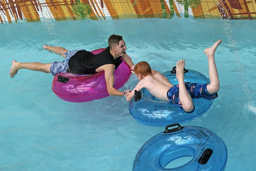 A man holds onto a youn boy as the pair play in a watercourse at Dreamworks Water Park inside the American Dream Mall, Thursday, Oct. 1, 2020, in East...