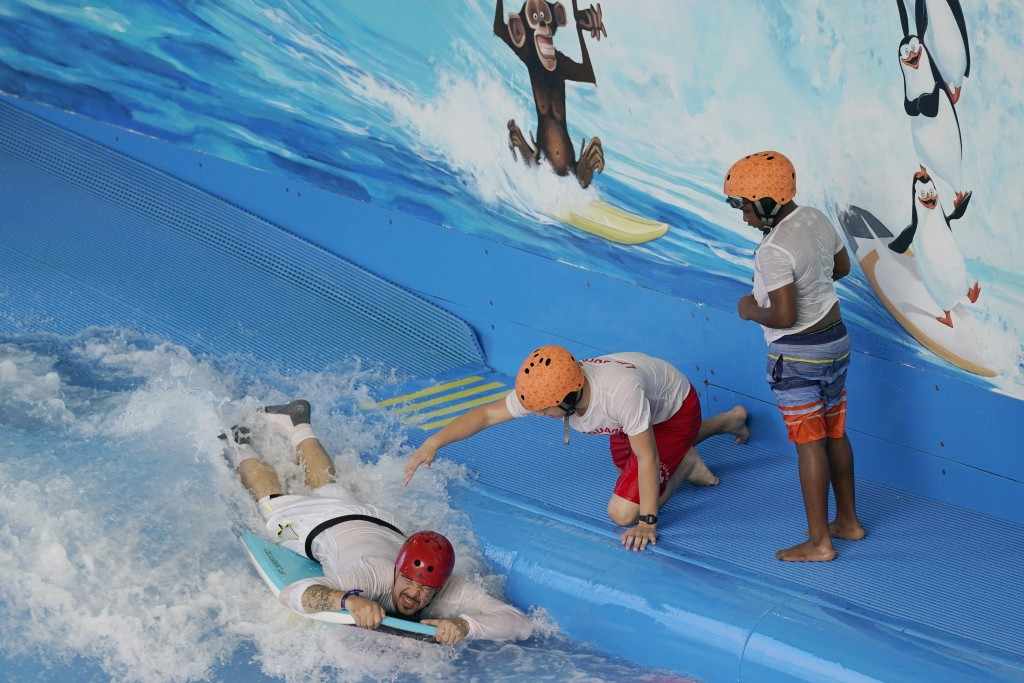 A youngster watches as a lifeguard releases a man riding a manufactured wave in the Dreamworks Water Park inside the American Dream Mall, Thursday, Oc...