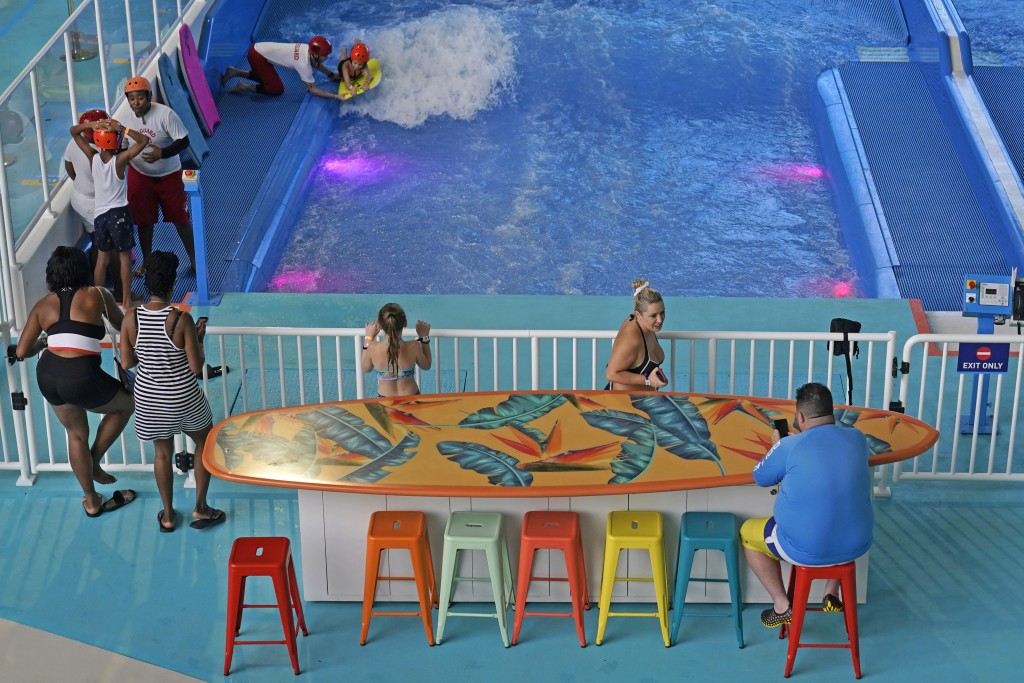 People sit at a surfboard table as others wait for a turn riding waves inside the Dreamworks Water Park at the American Dream Mall, Thursday, Oct. 1, ...