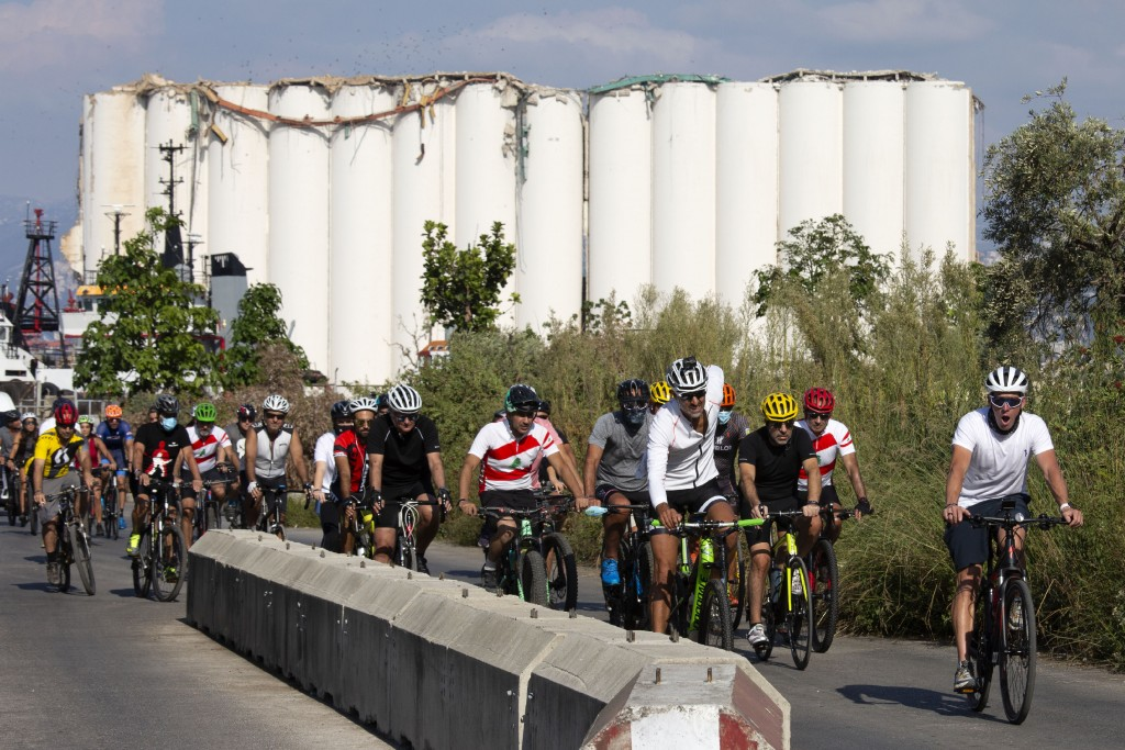Former American professional cyclist Lance Armstrong, right, rides with Lebanese and foreign cyclists at the site of the Aug. 4 deadly blast in the po...