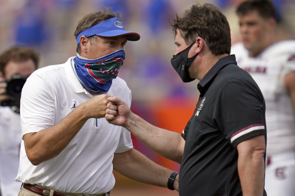 Florida head coach Dan Mullen, left, and South Carolina head coach Will Muschamp bump fists at the end of an NCAA college football game, Saturday, Oct...