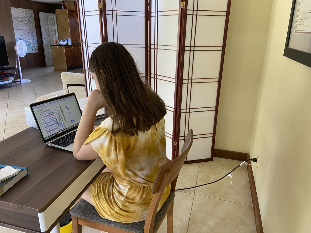 This photo provided by Adrienne Robillard shows her daughter, name withheld by parent, doing school work at a computer at home in Kailua, Hawaii, Frid...