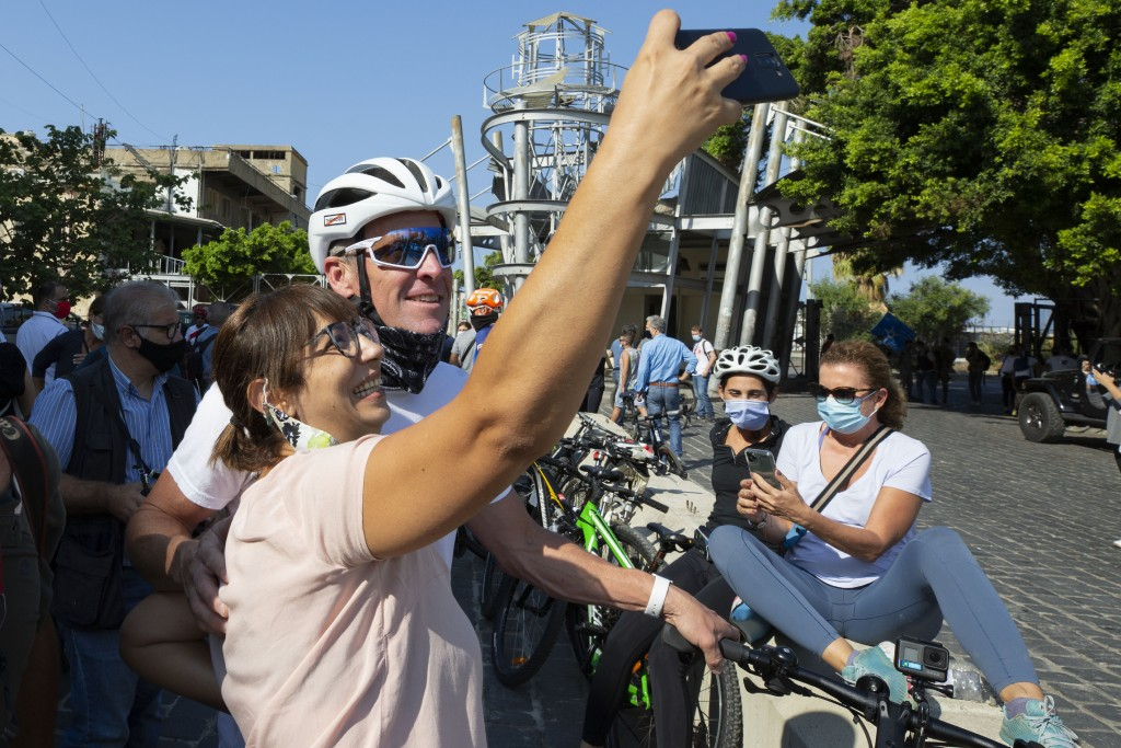 Former American professional cyclist Lance Armstrong, background, poses for a selfie before he rides with Lebanese and foreign cyclists at the site of...