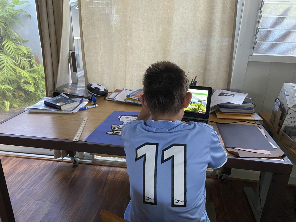 This photo provided by Adrienne Robillard shows her son, name withheld by parent, doing school work at a computer at home in Kailua, Hawaii, Friday, S...