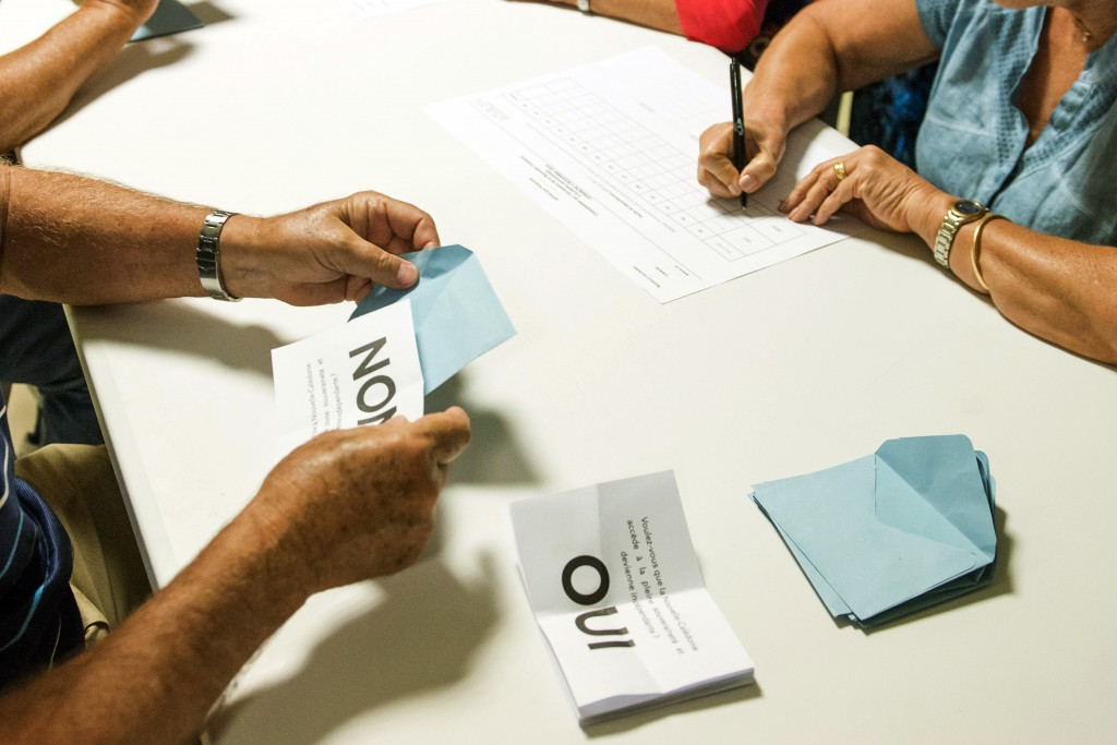 FILE - In this Nov. 4, 2018 file photo, polling station officials count the votes as part of the independence referendum in Noumea, the New Caledonia'...