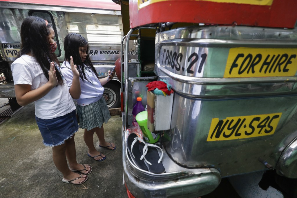 """Grade school students Bhea Joy Roxas, right, and Elrich Joy, left, use a smart phone as they raise their hands while reciting the """"Panatang Makabayan""""..."""