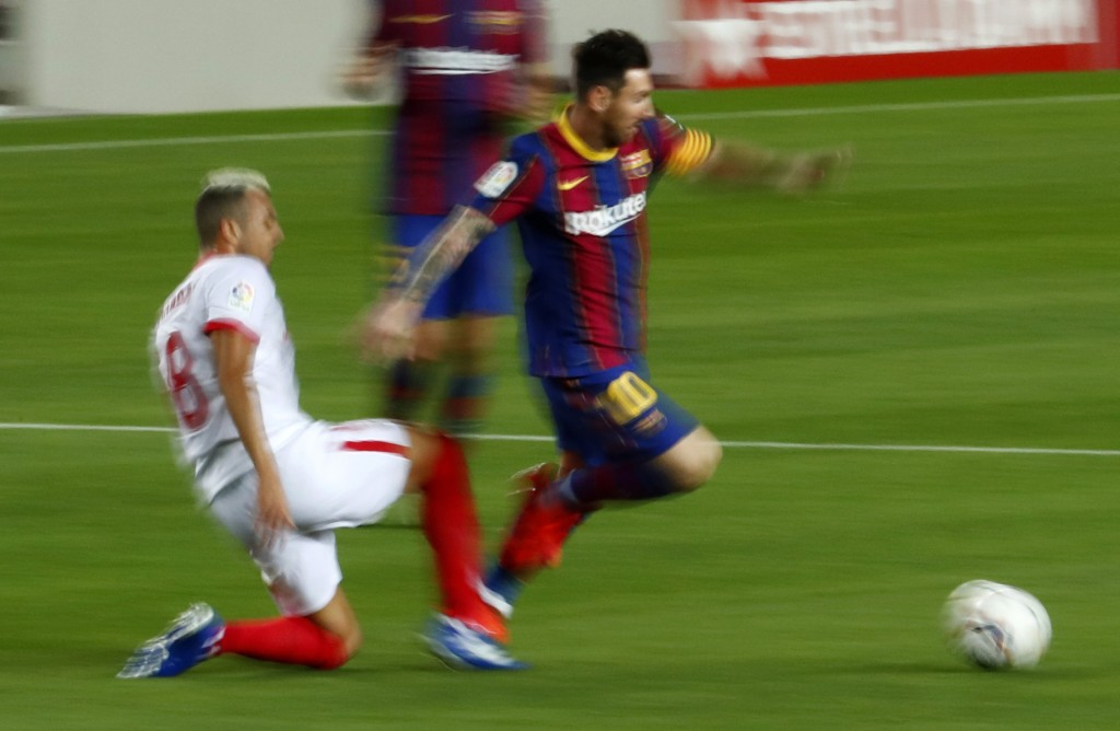 Barcelona's Lionel Messi is tackled by Sevilla's Joan Jordan during the Spanish La Liga soccer match between FC Barcelona and Sevilla FC at the Camp N...