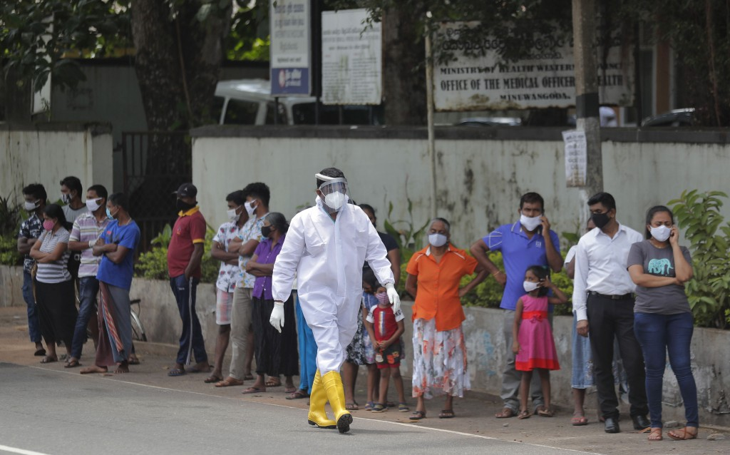 Sri Lankans wait to give swab samples to test for COVID-19 outside a hospital as a health official walks past in Minuwangoda, Sri Lanka, Tuesday, Oct....