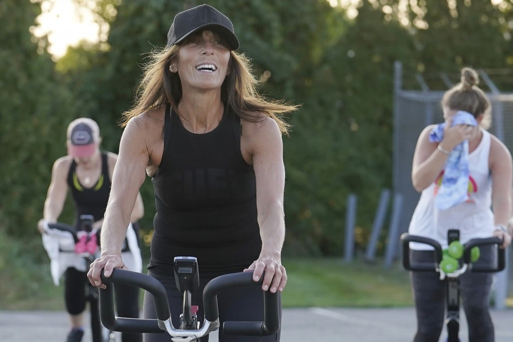 Jeanne Carter, co-owner of Fuel Training Studio, in Newburyport, Mass., front, works out on a stationary exercise bike during a spinning class in a pa...