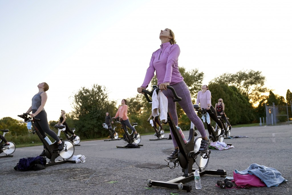 Donna Coskren, of Newburyport, Mass., front, stretches with others while on stationary exercise bikes during a spinning class in a parking lot outside...